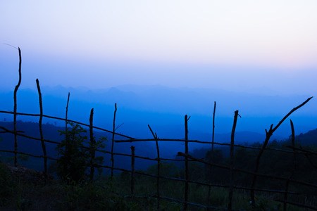 dark sky: The blue sky at sunset, Fence in shadow at foreground.Mountain on background.Sun nearly go down.