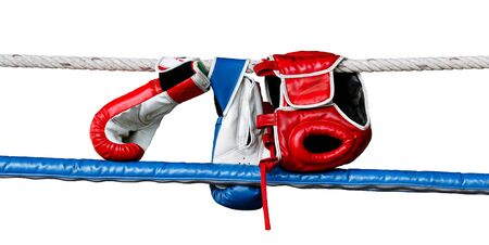 Boxing gloves and headguard hang on boxing ring rope.White isolate background. Standard-Bild