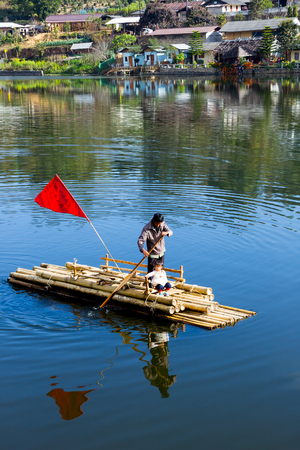 well known: CHIANG MAI, THAILAND - APRIL 16, 2015 : Father push the bamboo raft across river with his daughter in china village at north of Thailand. Editorial
