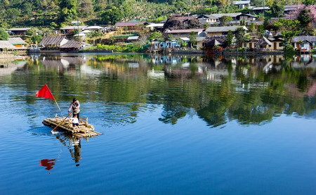 rafter: CHIANG MAI, THAILAND - APRIL 16, 2015 : Father push the bamboo raft across river with his daughter in china village at north of Thailand. Editorial
