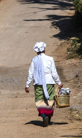 CHIANGMAI, THAILAND - JANUARY 16, 2015 : North of Thailand, Native woman in tradition dress style walk back home after plentifully offer food to monk at temple.