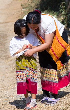 CHIANGMAI, THAILAND - JANUARY 16, 2015 : North of Thailand, Native mother and daughter in tradition dress style after plentifully offer food to monk at temple. Editorial