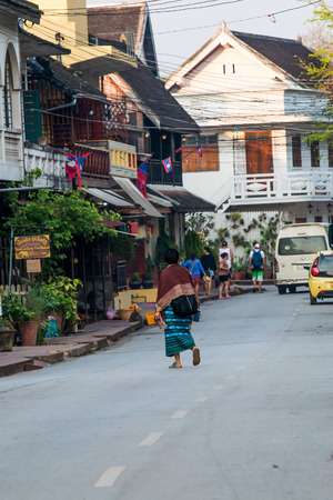 plentifully: LUANG PRABANG,LAOS - 12 APRIL 2015 :  Laos women back home after offer food to monk.Every day laos people plentifully offer food to monk that is charm and attract for tourist.