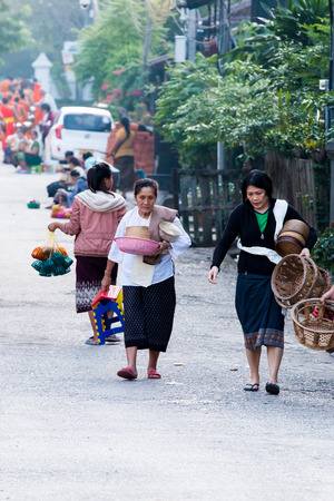 LUANG PRABANG,LAOS - 12 APRIL 2015 :  Laos women back home after offer food to monk.Every day laos people plentifully offer food to monk that is charm and attract for tourist.