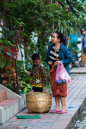 peddle: LUANG PRABANG,LAOS - 12 APRIL 2015 :  Laos women and her son walk along footpath to peddle local foodstuff, Ethnic food  in Louang Phabang is one of the interest for tourist. Editorial