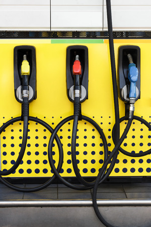 benzine: Fuel nozzle in gas station.Another color of fuel nozzle for  benzine,gasoline and diesel. Stock Photo