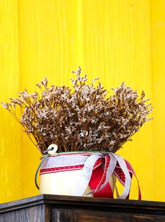 bunchy: Bouquet flower in flowerpot,Stand on yellow background.Red ribbon tied around flowerpot.