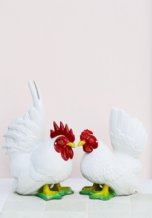 bantam hen: Two white bantam ceramic doll stand on tile, close up shot. Stock Photo