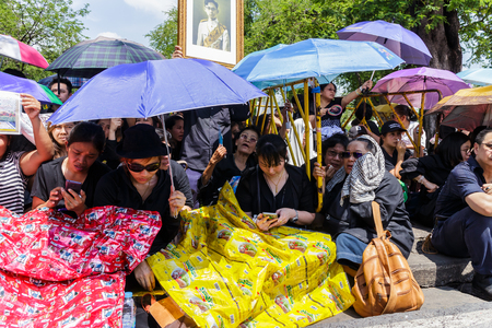 kingly: Bangkok, Thailand - October 14, 2016 :  Thai people are wearing black, white or dark coloured clothes during the mourning period for the funeral of His Majesty King Bhumibol Adulyadej.