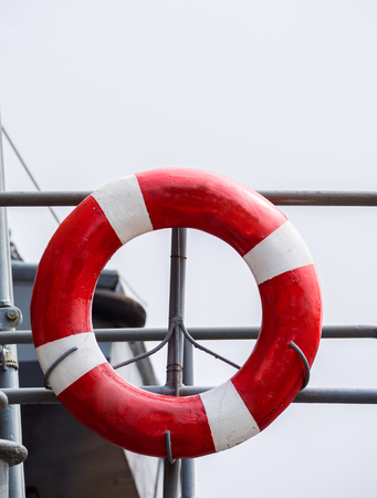 The lifebuoy hang on ship. background is white sky. Stock Photo
