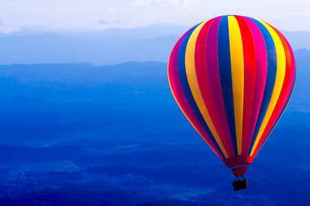 Colorful hot air balloon float on the sky. Background are blue mountain. Stock Photo
