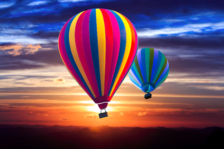 dazzlingly: Two hot air balloon float on the dazzlingly  sky at sunrise. Sunshine on mountain at background.