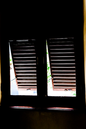 louvered: The old wooden louvered window in dark shadow. Stock Photo