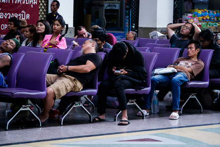 whacked: BANGKOK, Thailand - January 6, 2017: Exhausted passengers, weakly sleep while wait for the train at railway station. Editorial