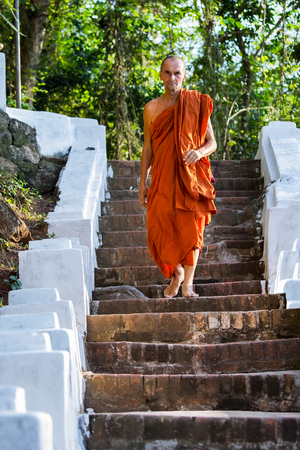 LUANG PRABANG, LAOS - APRIL 12, 2015 : European buddhist monk in Luang Prabang, The world heritage Country.