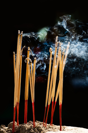 The joss stick smoke in the chinese shrine with dark background. 免版税图像