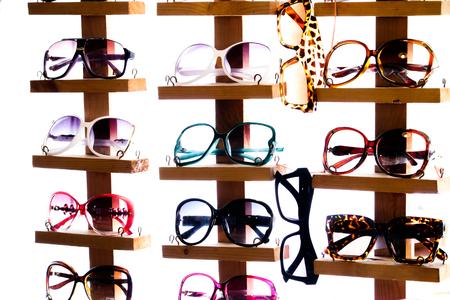 Many colorful fashion sunglasses lay on the shelf.