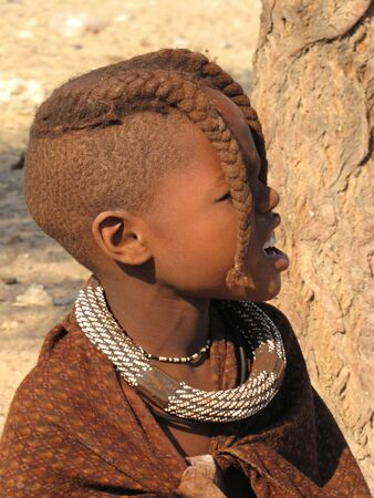NAMIBIA, KAOKOVELD, AUGUST 29: Himba girl presenting her braids in the village of Himba people near Opuwo in northern Namibia, August 29, 2009, Namibia