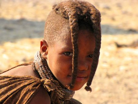 NAMIBIA, KAOKOVELD, AUGUST 29: Himba girl looking to the camera in the village of Himba people near Opuwo in northern Namibia, August 29, 2009, Namibia