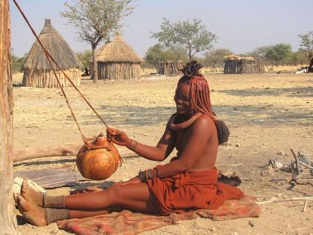 NAMIBIA, KAOKOVELD, AUGUST 29: Himba woman is making butter in the village of Himba people near Opuwo in northern Namibia, August 29, 2009, Namibia