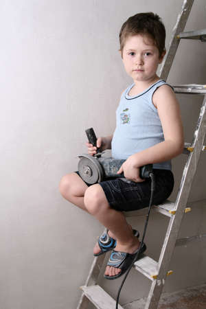 Boy on the ladder with circular saw photo