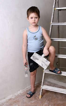 Boy with palette-knife near a ladder photo