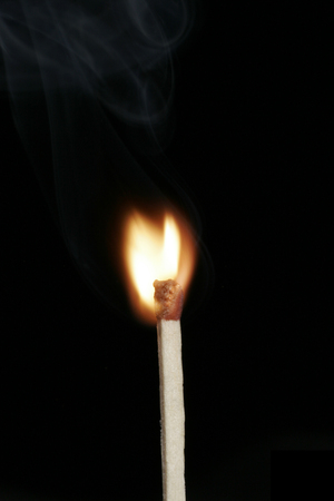 Burning Flame On A Single Matchstick On A Black Background photo