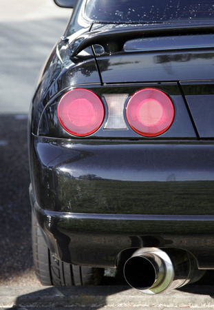 Car Detail - Red Rear Lights And Large Exhaust Of A Black Sports Automobile photo