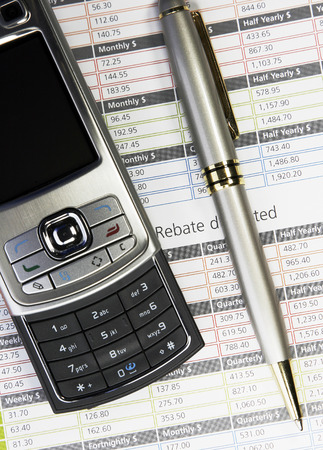 financials: Modern Small Silver Mobile Phone And Pen On A Business Background, Communication Technology