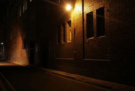 city alley: Mysterious Alley - Dark Abandoned Street With Lights Shining On A Brick Wall Stock Photo