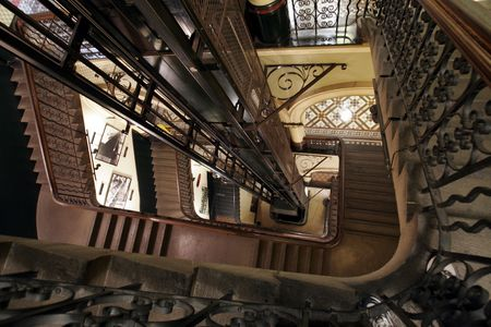 Looking Down A Staircase With An Elevator In The Centre