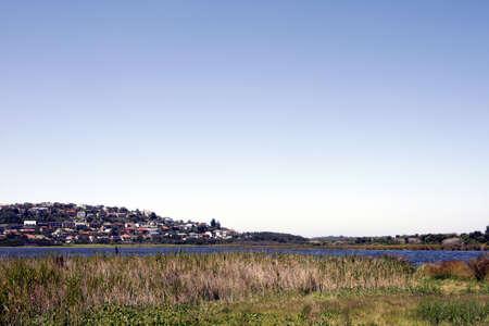 suburbian: Grass, Lake, Hill, Houses Gradient Clear Blue Sky In A Sydney Suburb, Australia Stock Photo