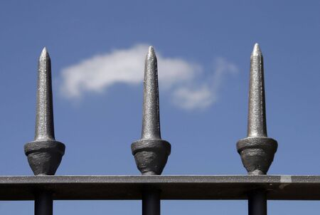 Grey Metal Fence Top In Front Of Clear Blue Sky, One White Cloud photo