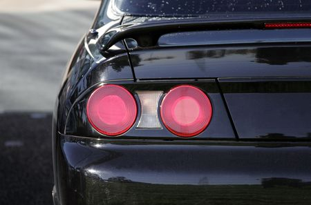 Car Detail - Red Rear Lights Of A Black Sports Automobile