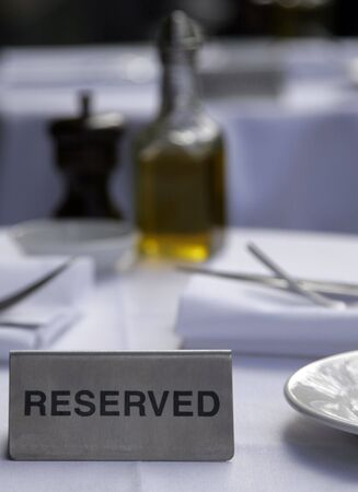 reserved sign: Metallic Silver Reserved Sign On A Restaurant Table Stock Photo