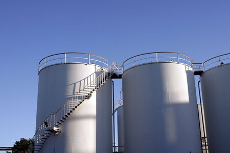 Two Industrial Silo Tanks, Clear Blue Sky Background Stock Photo