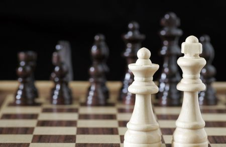 White Chess King And Queen In Focus, Black Pieces OOF Stock Photo