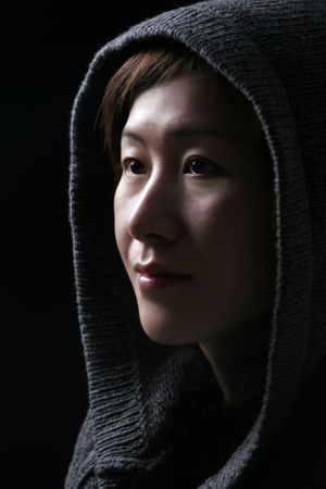 Asian Woman In Deep Thoughts - Hood Over Head - Black Background photo