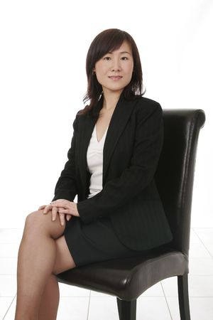 Beautiful Young Asian (Chinese) Businesswoman Sitting On Dark Leather Chair photo
