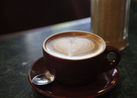 Dark Coffee Cup With Heart Shape Foam On Table - Focus On Front Stock Photo