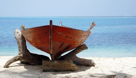 A Small Red wooden Boat On A Sunny Ocean Beach Stock Photo - 9292290