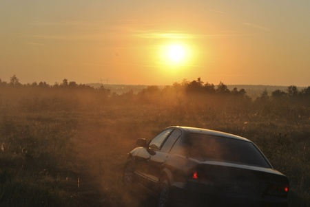 The car traveling on a rural road through a misty haze in the direction of the dawn sun photo
