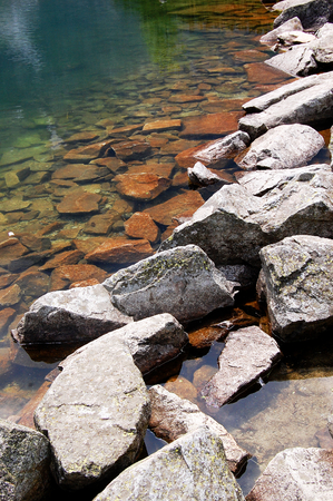 submerge: Sharp rocks on the shore of a mountain lake Stock Photo