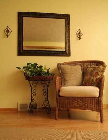 Natural space created with wood floor, wicker chair and plant stand photo
