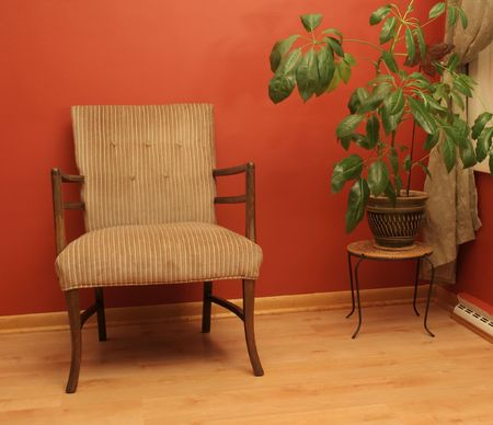 Arm chair and plant against red wall Banco de Imagens