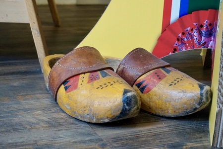 Old painted Dutch wooden clogs with a leather strap, on the floor of a tourist shop, next to a display stand. A bit of the cardboard of the display stand shows. Painted in yellow, red and black.