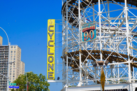 Famous Cyclone roller coaster at Coney Island in New York, a historic landmark. Shows side view of the curved tracks and white rails. Engineering structure. 에디토리얼