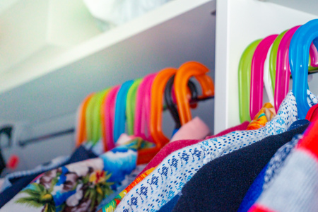 Colorful kid's hangers with toddler boy's shirts hanging in a closet. Archivio Fotografico