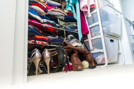 Armario de apartamento real organizado y lleno de ropa de mujer, que muestra las compras, los hábitos de vida, la vida real y las elecciones de ropa de una persona a la moda.