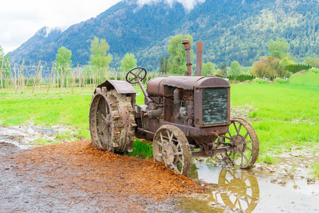 Vintage tractor farm equipment on a real farm, rusted and broken down, parked in mud, but a historical remnant on display.